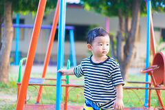 Sad little Asian kid at the playground under the sunlight in sum. Mer, Kids play on school yard. shallow DOF Royalty Free Stock Photos