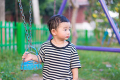 Sad little Asian kid at the playground under the sunlight in sum. Mer, Kids play on school yard. shallow DOF Stock Photography