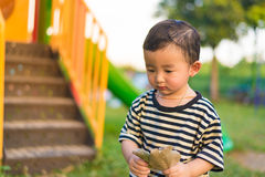 Sad little Asian kid at the playground under the sunlight in sum. Mer, warm tone, shallow DOF Royalty Free Stock Images