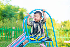 Sad little Asian kid sitting on slide at the playground at the d. Sad little Asian kid sitting on slide at the playground under the sunlight in summer, Kids play Royalty Free Stock Images