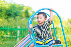 Sad little Asian kid sitting on slide at the playground at the d. Sad little Asian kid sitting on slide at the playground under the sunlight in summer, Kids play Royalty Free Stock Image