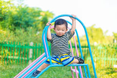 Sad little Asian kid sitting on slide at the playground at the d. Sad little Asian kid sitting on slide at the playground under the sunlight in summer, Kids play Royalty Free Stock Photos