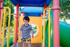 Sad little Asian kid on slide at the playground at the day time. Sad little Asian kid on slide at the playground under the sunlight in summer, Kids play on Royalty Free Stock Photo