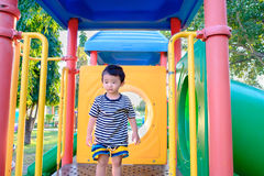 Sad little Asian kid on slide at the playground at the day time. Sad little Asian kid on slide at the playground under the sunlight in summer, Kids play on Royalty Free Stock Images