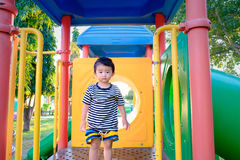 Sad little Asian kid on slide at the playground at the day time. Sad little Asian kid on slide at the playground under the sunlight in summer, Kids play on Stock Image