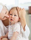 Sad little baby girl comforted by her mother Stock Photo