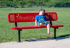 Sad little boy alone on a buddy bench. A sad lonely little boy sits on a buddy bench waiting for a friend to notice he is alone. concept of a buddy bench is kids royalty free stock photography