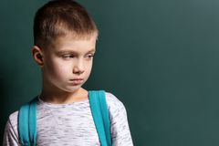 Sad little boy being bullied at school. On color background royalty free stock photo