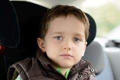 Sad little boy in car safety seat. Royalty Free Stock Photos