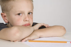 Sad little boy doing his homework. Royalty Free Stock Photo