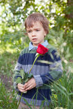 Sad little boy holding red rose in her hand,  park Stock Photo