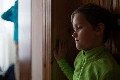 Sad little boy at home. Stock Photos