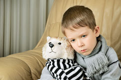 Sad little boy hugging toy dog Stock Photo