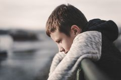 Sad little boy leaning over railing Stock Photos