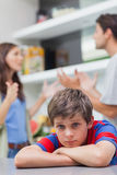 Sad little boy listening to his parents arguing. In the kitchen Stock Photography