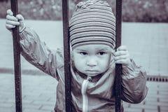 Sad little boy looks through a lattice.  Stock Photo