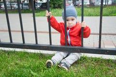 Sad little boy looks through a lattice.  Stock Photography