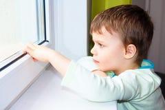 Sad little boy looks out the window. Portrait of Caucasian boy near window. Melancholic child. Sad little boy looks out the window. Portrait of Caucasian boy Stock Image
