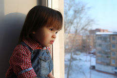 Sad little boy looks out of window in wintertime. Lovely little boy (2 years) looks out of window in wintertime Royalty Free Stock Photography