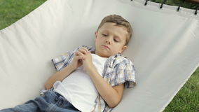 Sad little boy lying on the hammock stock footage