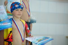 Sad little boy with a medal for swimming royalty free stock image