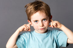 Sad little boy not willing to listen to domestic violence. Sad little boy with blue eyes and freckles not willing to listen to domestic violence or parent Royalty Free Stock Images