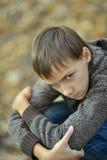 Sad little boy outdoors in autumn. Portrait of a sad little boy outdoors in autumn Royalty Free Stock Photos