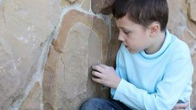 Sad little boy outdoors stock video