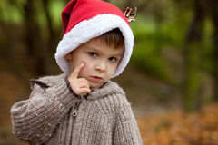 Sad little boy in the park, with santa hat, showing his hurt che Stock Image
