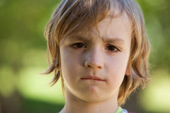 Sad little boy in the park Stock Photo