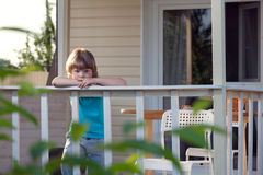 Sad little boy on the porch of rural house Stock Photos