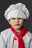 Sad, little boy preparing healthy food on kitchen over grey back Stock Photos