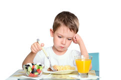 Sad little boy sits at the dining table and lookin Stock Photos
