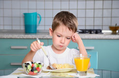 Sad little boy sits at the dining table and looking in the plate Royalty Free Stock Photography