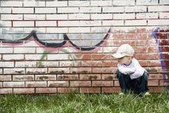 Sad little boy sits near a brick wall Stock Image