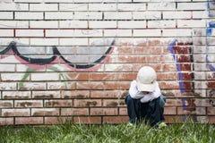 Sad little boy sits near a brick wall Royalty Free Stock Photos