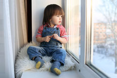 Sad little boy sits on sill and looks out of window. In wintertime Royalty Free Stock Photos