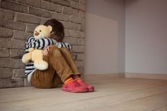 Sad little boy sitting against the wall in despair. In his hands he holds an old friend teddy bear Royalty Free Stock Image