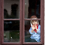Sad little boy, sitting behind the window Royalty Free Stock Photos