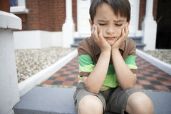 Sad Little Boy Sitting On Front Steps. Sad little boy with hands on chin sitting on front steps of house Royalty Free Stock Photography