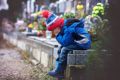 Sad little boy, sitting on a grave in a cemetery stock photo