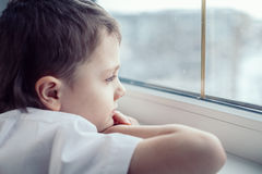 Sad little boy sitting near the window. One sad little boy sitting near the window at the day time. Concept of sorrow stock photo