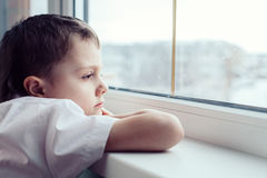 Sad little boy sitting near the window. One sad little boy sitting near the window at the day time. Concept of sorrow stock photography