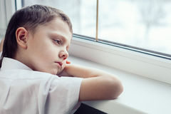 Sad little boy sitting near the window. One sad little boy sitting near the window at the day time. Concept of sorrow royalty free stock photography