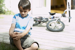Sad Little Boy Sitting On Porch Of House Royalty Free Stock Photo