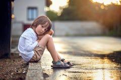 Sad little boy, sitting on the street in the rain, hugging his t. Eddy bear, summertime on sunset royalty free stock photo