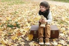 Sad little boy sitting on suitcase in the autumn park Stock Photos