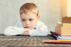 Sad little boy sitting at the table. Bored pupil. Tired bored little boy sitting sadly at the table with books by his side Royalty Free Stock Photos