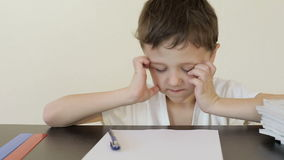 Sad little boy sitting at the table and doing homework. Concept of bad study stock video footage