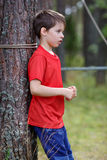 Sad little boy standing under the tree Stock Images